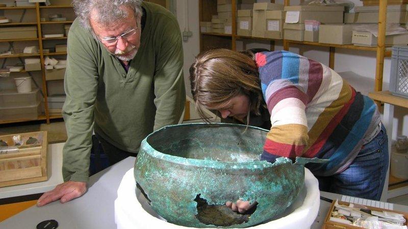 Paleobotanisti ottaa pronssiastiasta näytettä analyysia varten.